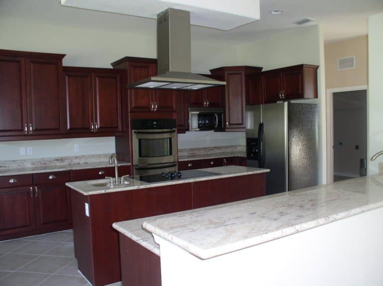 red wooden kitchen cabinets and kitchen island with whitemarble countertops