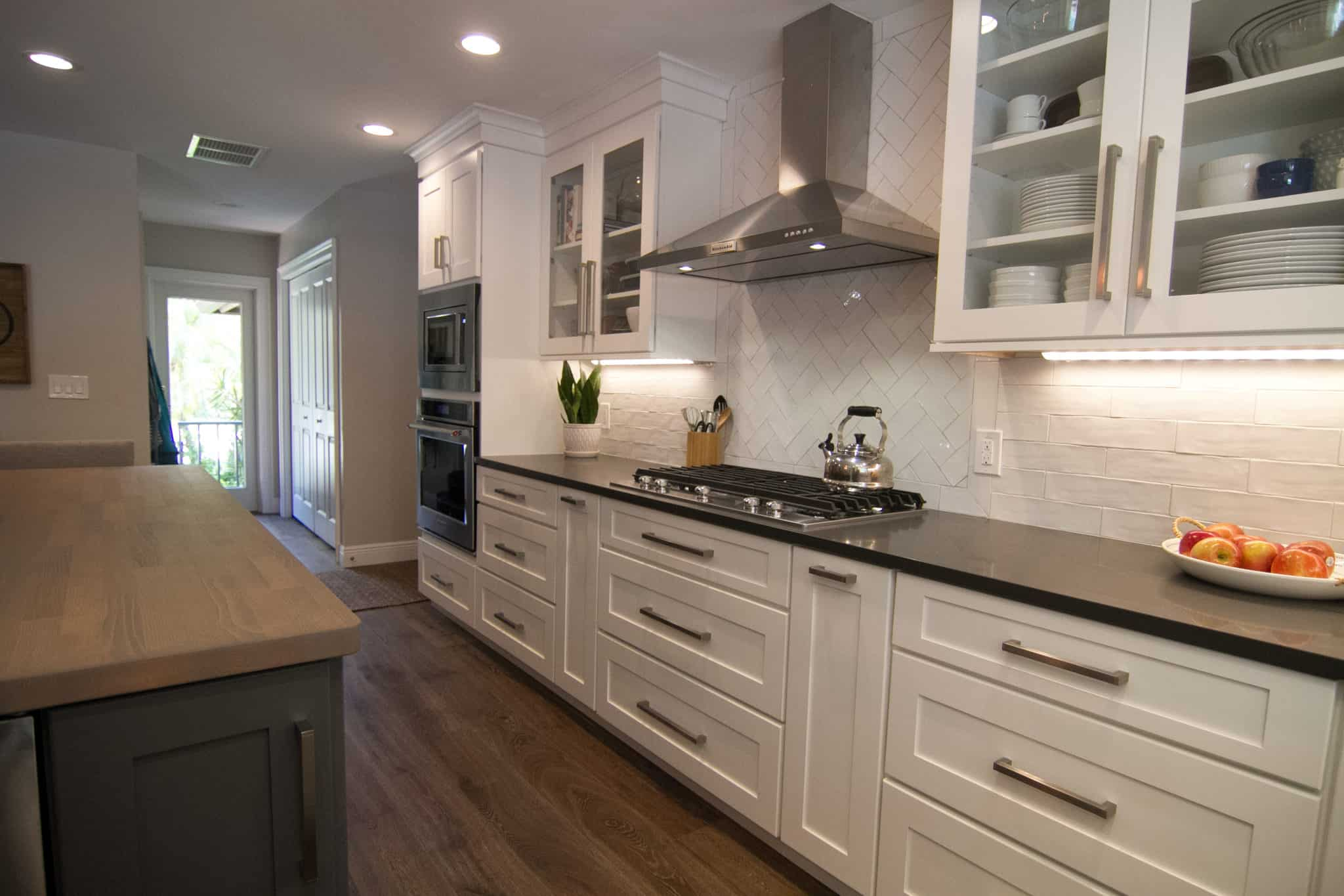 white cabinets with large stell hood